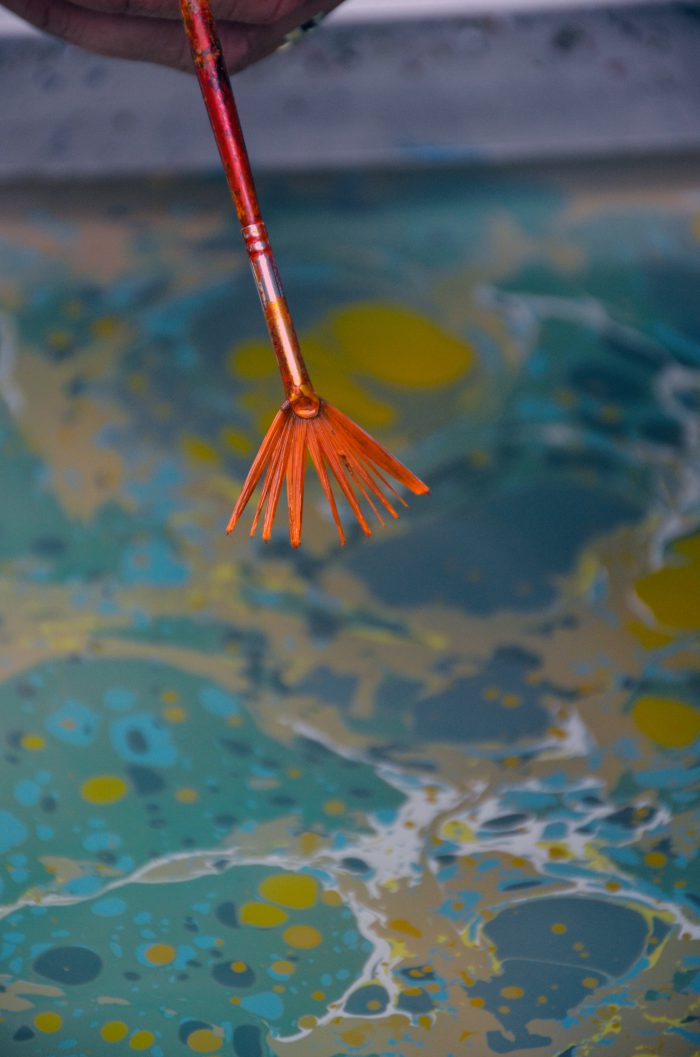 paint is sprayed on the surface of the marbling bath
